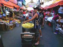Aziatische straatventer die gestoomd graan op een maïskolf in quiapo, Manilla, Filippijnen in Azië verkopen stock foto's