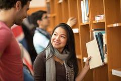 Aziatische student die boeken in bibliotheek kiezen Stock Afbeelding