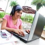 Aziatische student die haar notitieboekjecomputer met behulp van Royalty-vrije Stock Afbeeldingen
