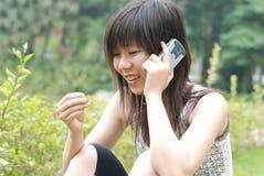 Aziatische student op celtelefoon Royalty-vrije Stock Afbeeldingen