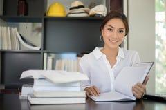Aziatische studente die en een boek voor ontspanning glimlachen lezen stock foto