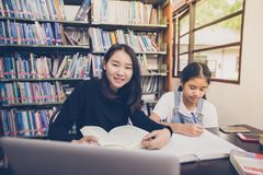 Aziatische studenten die boeken in de bibliotheek lezen royalty-vrije stock afbeelding