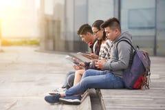 Aziatische Studenten die in openlucht zitten royalty-vrije stock foto
