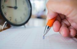 Aziatische Studenten die optische vorm van gestandaardiseerde examens nemen dichtbij Al Stock Afbeelding