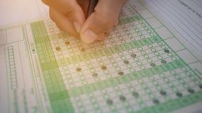 Aziatische Studenten die potlood in hand het doen meerkeuzequiz houden Stock Fotografie