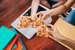 Aziatische studenten die samen etend de pizza eten stock foto