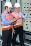 Aziatische technici bij paneel op bouwwerf Stock Foto