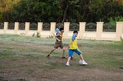 Aziatische Thaise vader opleidend en speelvoetbal of voetbal met zoon bij speelplaats op yard in openbaar tuinpark in Thailand stock afbeelding