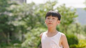 Aziatische tiener die en zich in openlucht in tuin in ochtend glimlachen bevinden Royalty-vrije Stock Afbeelding