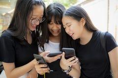 Aziatische tiener die met de lezingsbericht van het gelukgezicht lachen in het smartphonescherm royalty-vrije stock foto