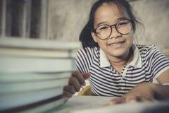 Aziatische tiener die oogglazen dragen die het huiswerk met stapel doen van royalty-vrije stock fotografie