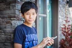 Aziatische tiener die smartphone, communicatietechnologie gebruiken stock foto's