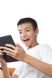Aziatische tiener die zijn tablet met gelukkig gevoel gebruiken Royalty-vrije Stock Foto