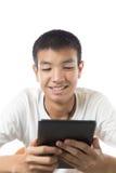 Aziatische tiener die zijn tablet met glimlach gebruiken Stock Afbeelding