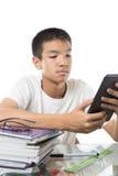 Aziatische tiener die zijn tablet over de stapel van boeken gebruiken Royalty-vrije Stock Foto's