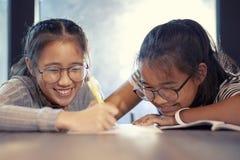 Aziatische tiener door pen op Witboek schrijven en het toothy glimlachen die met gelukemotie stock foto