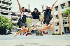 Aziatische tiener drie die medio lucht met gelukemotie springen tegen de schoolbouw achtergrond stock foto