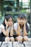Aziatische tiener twee die hand gebruiken dicht haar oor voor luisteren niet stock fotografie