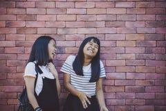 Aziatische tiener twee die met gelukemotie statusagai lachen stock foto's
