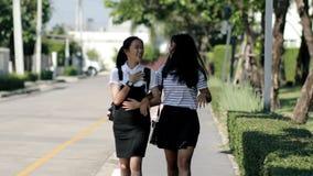 Aziatische tiener twee die op de straat van het huisdorp lopen stock videobeelden