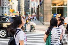 Aziatische toeristen die de weg, NYC kruisen stock foto's
