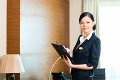 Aziatische uitvoerende huishoudster het controleren hotelruimte Stock Afbeelding