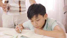 Aziatische vader die & zijn die tiener spreken adviseren met thuiswerk wordt gefrustreerd Stock Foto