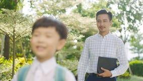 Aziatische vader die zijn zoon accompnying die naar school in de ochtend gaan Royalty-vrije Stock Foto's