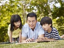 Aziatische vader en kinderen die boek samen lezen Royalty-vrije Stock Foto's