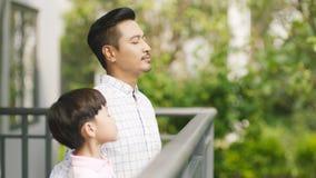 Aziatische vader en zijn zoon die zich op balkon bevinden die van verse aard genieten Royalty-vrije Stock Afbeeldingen