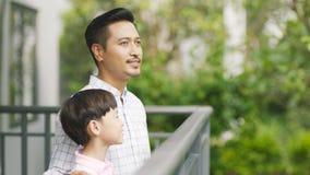 Aziatische vader en zijn zoon die zich op balkon bevinden die van verse aard genieten Stock Foto's