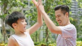 Aziatische vader & zoon die een hoogte vijf na het noteren in openlucht in ochtend geven Stock Foto's