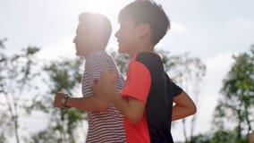 Aziatische vader & zoonsjogging in openlucht in de terug aangestoken ochtend Stock Foto's