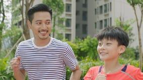 Aziatische vader & zoonsjogging in openlucht in tuin in de ochtend Royalty-vrije Stock Afbeelding
