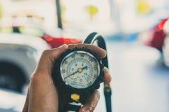 Aziatische van de de inspectiemaatregel van de mensenauto Opgeblazen Rubber de bandenauto hoeveelheid Sluit omhoog Opgeblazen de  stock foto