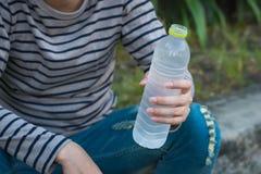 Aziatische van de mensenzitting en holding fles water stock foto