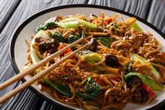 Aziatische vegetarische voedsel udon noedels met choy baby bok, shiitake paddestoelen, sesam en peperclose-up op een plaat horizo royalty-vrije stock fotografie