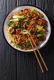 Aziatische vegetarische voedsel udon noedels met choy baby bok, shiitake paddestoelen, sesam en peperclose-up op een plaat Vertic stock foto's