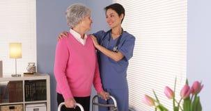 Aziatische verpleegster en bejaarde patiënt die zich door venster bevinden Royalty-vrije Stock Foto's