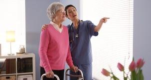 Aziatische verpleegster en bejaarde patiënt die zich door venster bevinden Stock Afbeeldingen