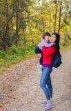 Aziatische verschijningsmoeder die met haar kind in warme zonnige de herfstdag lopen stock afbeelding