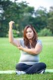 Aziatische vette vrouw die haar wapenvet controleren stock foto's