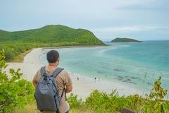 Aziatische vettige backpackertribune op meningspunt bovenop het eiland met de oceaan en blauwe hemel van het idyllicestrand in va stock foto's