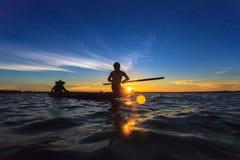 Aziatische visser op houten boot die een net voor het vangen gieten Royalty-vrije Stock Afbeelding
