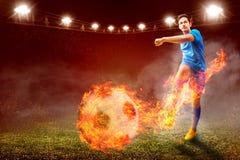 Aziatische voetbalstermens in blauw Jersey met het schoppen van de bal met brandeffect stock foto's