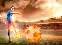 Aziatische voetbalstermens in blauw Jersey met het schoppen van de bal met brandeffect royalty-vrije stock foto's