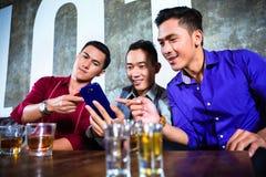 Aziatische vrienden die schoten in nachtclub drinken stock afbeelding