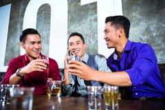 Aziatische vrienden die schoten in nachtclub drinken royalty-vrije stock afbeeldingen