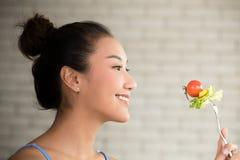 Aziatische vrouw in blije houdingen met de salade van de handholding op vork royalty-vrije stock fotografie