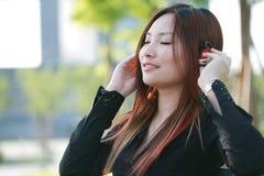 Aziatische vrouw die aan de muziek luistert Stock Afbeeldingen